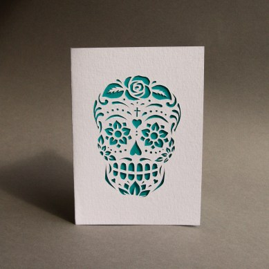 A calavera design cut out of white card, with a turquoise backing, consisting of flowers, hearts and swirls