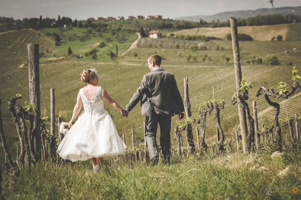 Emma & Alex walk through the vineyards in the Chianti hills