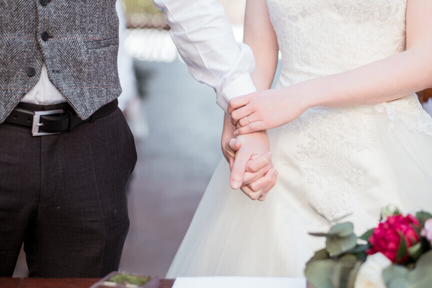 The groom and the bride shake hands during the ceremony
