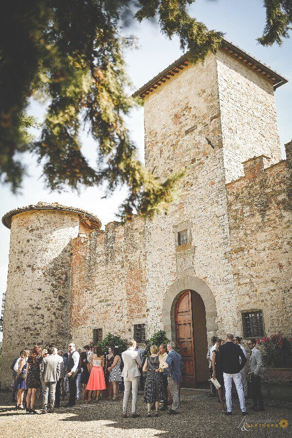 Guests await the bride and groom outside the castle