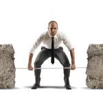 business man lifting 2 concrete blocks