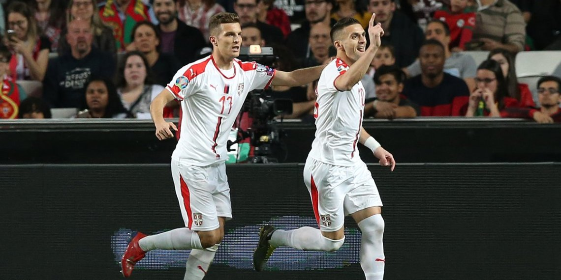 Dusan Tadic (R) wheels away in celebration after putting Serbia ahead against Portugal; home team medical staff attend an injured Cristiano Ronaldo (inset) in Lisbon, Monday