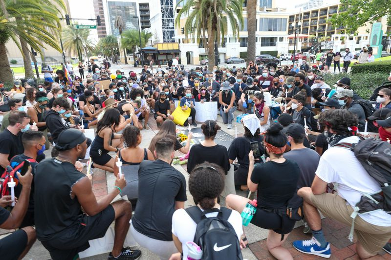 Protestors take a moment of silence at Lake Eola, before marching to Orlando Police Department Headquarters on Sunday, May 31, 2020, during ademonstrationdemanding justice forGeorge Floyd,the Minnesota man that died at the hands of police. (Rich Pope/ Orlando Sentinel)