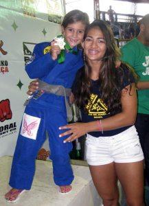 A pequena Maria Luisa no  pódio ao lado da jovem mestra Beatriz Mesquita. (Divulgação)