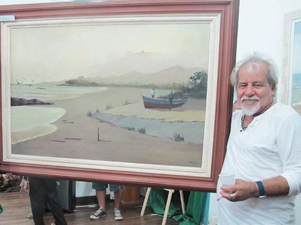 O artista plástico Nelsinho com uma de suas belas marinhas, inspirada na Praia de Itaúna (foto: Dulce Tupy)