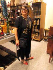 A jornalista Yuko Suzuki comprando uma sapatilha feita artesanalmente por Espedito Seleiro