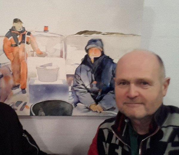 Sudas in front of one of Nirvi's ocean paintings.