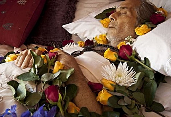 dead man surrounded by flowers