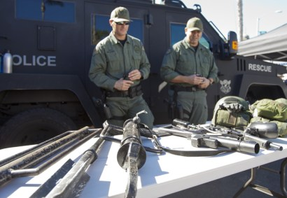Oceanside SWAT officers Davis Williams and Larry Weber stand in front of a table of tools from their trade which include a pepper ball gun, a rip ram and a break and rake.