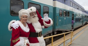 Mr and Mrs Claus wait for passengers to board the Coaster Holiday Express train