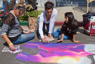 Avery Patefield, Raziah Roushan and Nevaeh Destiny create with water based pastels on the street in front of the Oceanside Museum of Art