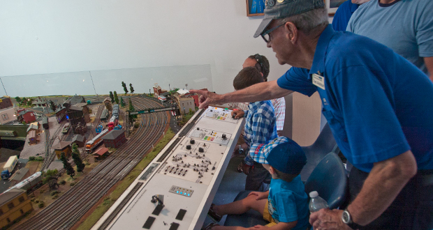"Tom ""Papa"" Ashton explains how the trains work to youngsters at the controls of the ""Trains for Kids"" working display"