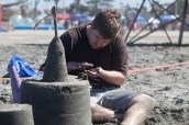 Zac Hawood works on a sand castle brick in the sand castle competition on Saturday