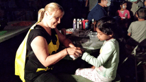 Laurie Minouei applies a tattoo to Stephanie, 7, at the Crown Heights Halloween Festival