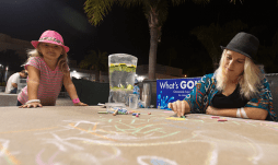 Hayden, 4, and Nikki Springer drawing in front of the library