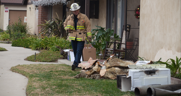 Oceanside Battalion Chief, Peter Lawrence inspects the debris pulled from the home.