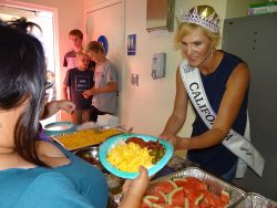 Mrs. California, Anamarie Dean of Encinitas, a regular volunteer at the Solutions for Change Intake and Access Center in Vista serves food she prepared to a hungry crowd of formally homeless families. (Click on image to enlarge photo) Courtesy photo