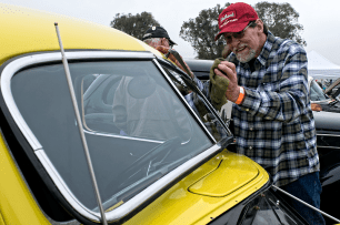 Ernie Eineman, owner of Ace Welding and a 1963 graduate of OHS polishes the windshield of his 1937 Ford Sedan Delivery.