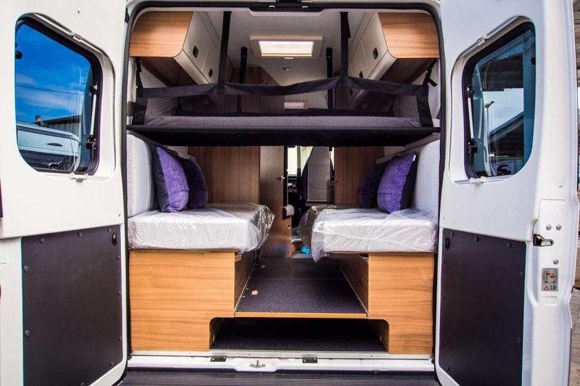 Vista trasera del dormitorio de camas gemelas con hamaca infantil en la Sun Living V65 SL.
