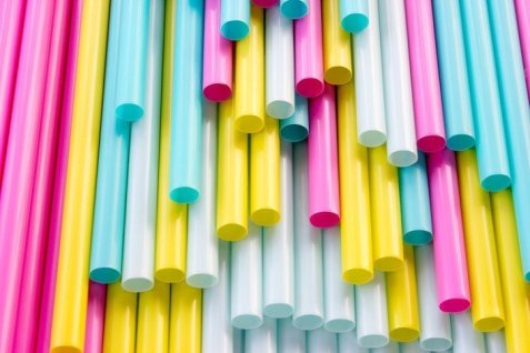 Many colorful straws stacked on top of each other.