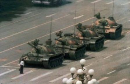 In this June 5, 1989 file photo, a Chinese man stands alone to block a line of tanks heading east on Beijing's Cangan Blvd. in Tiananmen Square. The man, calling for an end to the recent violence and bloodshed against pro-democracy demonstrators, was pulled away by bystanders, and the tanks continued on their way. (AP Photo/Jeff Widener, File)
