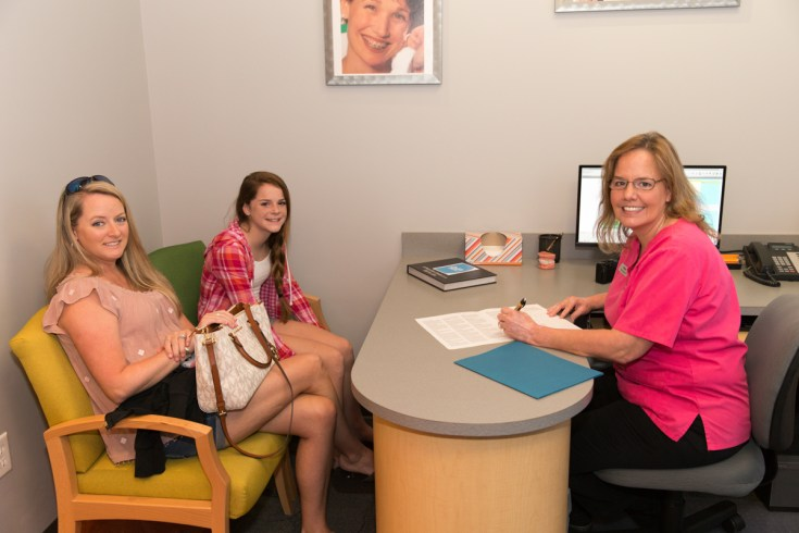 team member with patient and patients mother 001 Ossi Orthodontics Jacksonville and St. Augustine Florida Orthodontist