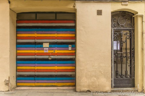 a colorful garage door and iron/glass door in Barcelona