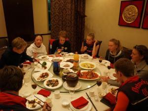 Kinesisk måltid der alle sitter rundt er rundt bord og plukker maten med pinner
