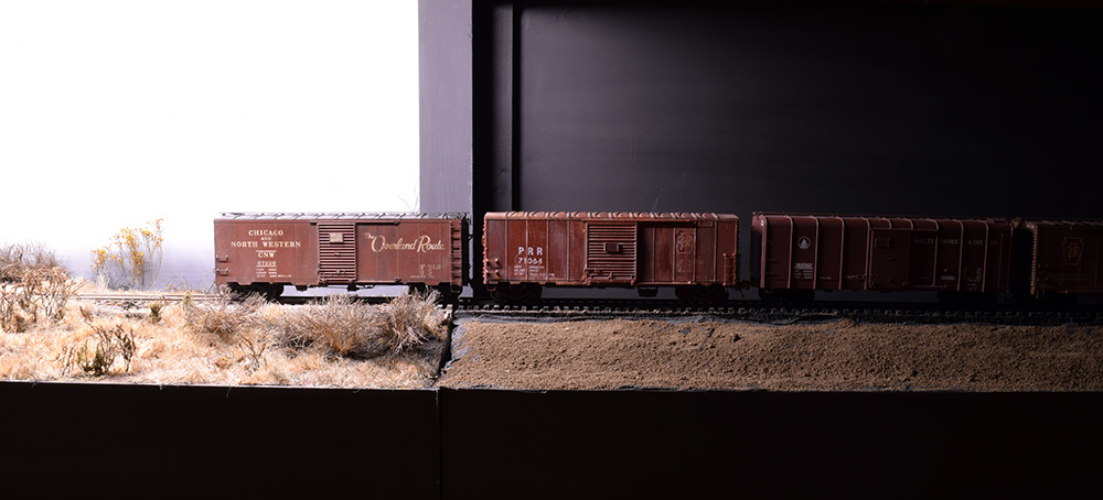 Freight cars bridge the zone from layout into staging area. Reduced light lets them fade into darkness.