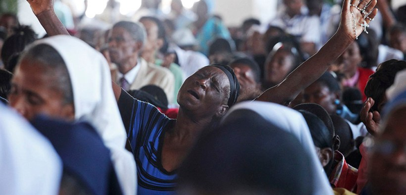 Woman prays inside rebuilt Port-au-Prince cathedral
