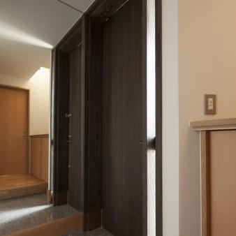 15:玄関(子) 木製玄関戸はタモ材で製作し、傷みやすい足元には銅板を巻いてある。
