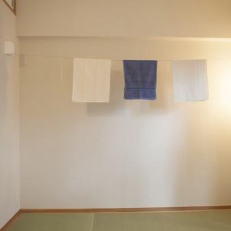 8:寝室 使うときだけ引き伸ばして使うワイヤー式の室内物干しが設置されている。