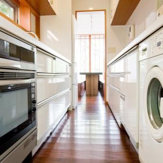 12:台所 台所。居間のテーブルと一直線に並んでいる。 左手はキッチン、右手は洗濯機やゴミ箱を組み込んでいる食器棚。
