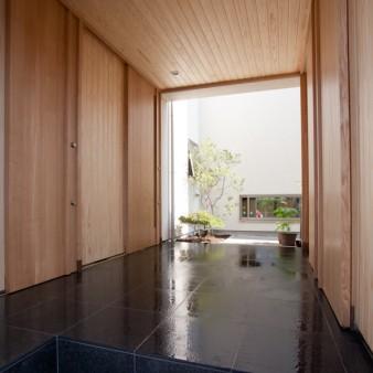 2:ポーチ 格子戸を開けると、連続した木製建具と一体になった空間が佇んでいる。 淡いグラデーションの光が落ちてくる正面は露地で、右手には車庫があり左手には玄関へと、人の流れをさばくジャンクションのような交通の要となるポーチ。 木製建具は全て引き戸としタモ材で製作している。壁、天井は杉の無垢板。