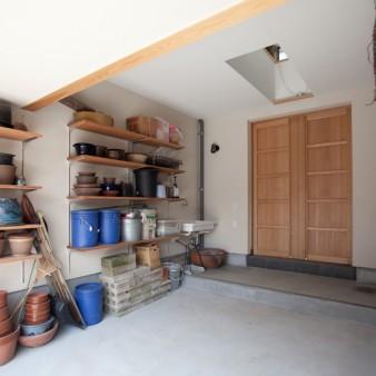 13:車庫 車庫の両脇には、園芸用品や陶芸用品などが収納出来るよう、可動棚の設置や外流しが設えてある。上部の開閉式ハイサイドライトからは、柔らかな光が落ちてくると共に自然換気を促すことができる。