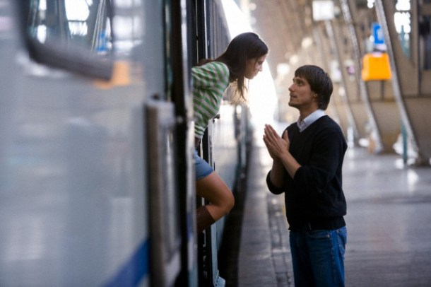 Man pleading with woman in train station