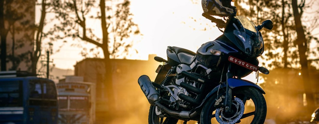 motorcycle on kickstand in the spring with helmet on handle