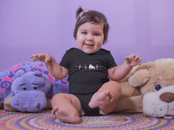 Otter Heartbeat Onesie on baby with stuffed animals Mockup in Black.