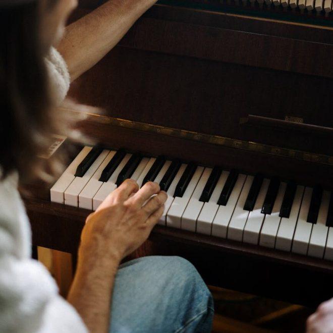 woman in white shirt playing piano