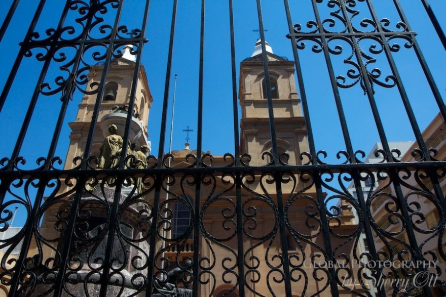An iron gate entry in front of a neighborhood church