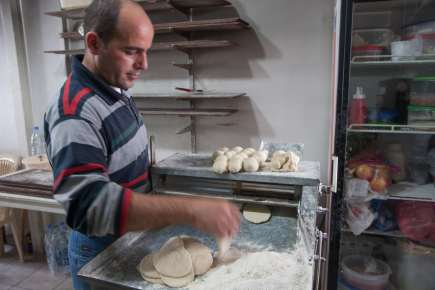 Lebanese shop owner making bread