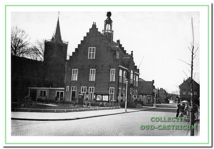 Dorpsstraat met links het gemeentehuis en plantsoen.