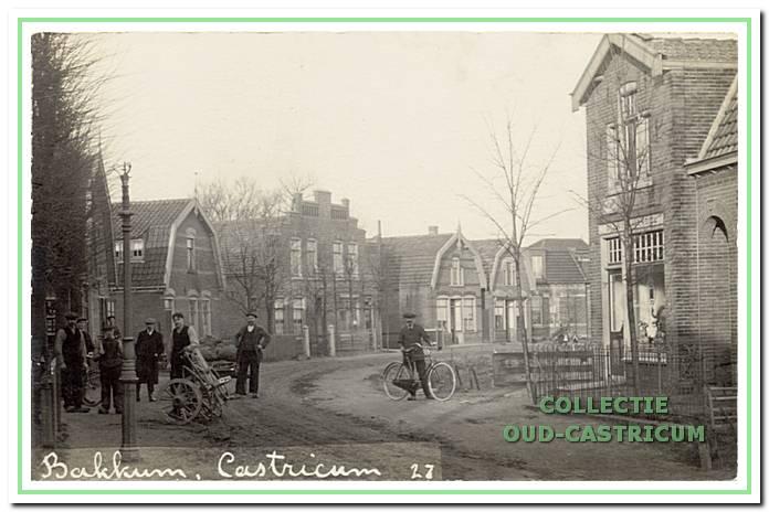 Uiterst links de smederij van Jan Hoebe (nr 102), daarna de timmerman Ber van Benthem (nr 104) en aannemer Cor de Groot in het met fraai metselwerk versierde pand. Op de foto de man met het onderstel van een wagen is Jan Hoebe en de man met de fiets is Herman Twisk van de rijwielzaak, die rechts op de foto is te zien.