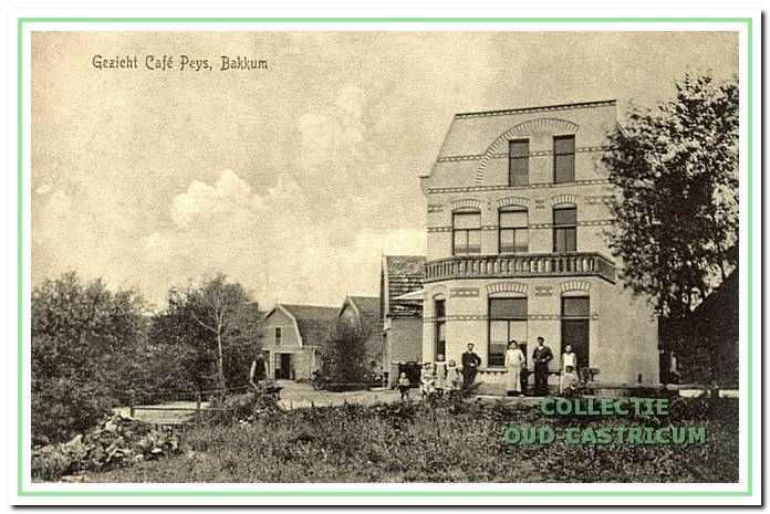 In dit grote witte gebouw had Klaas Peijs zijn café, dat in 1911 afbrandde. Voor het café staat de familie Peijs. Op deze plek zou kort daarna een textielzaak en hulppostkantoor verrijzen. Deze activiteiten gingen in de dertiger jaren over op respectievelijk de zoons Gerrit en Freek Peijs, die zich vestigden aan de overzijde van de Van Oldenbarneveldweg.