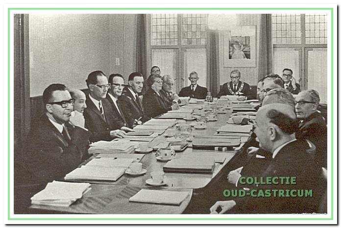 De vergaderzaal in het gemeentehuis met om de tafel geschaarde raadsleden in 1962.
