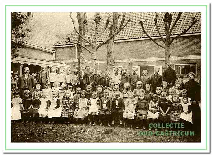 De oudst bekende foto van de jongste klassen van de dorpsschool, genomen op de binnenplaats rond 1900. Links het hoofd der school meester C.J. Bussen.