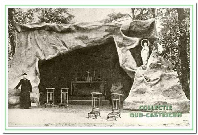 """Pastoor Engering poserend voor de """"Lourdesgrot"""" in de tuin van de pastorie ca. 1920."""