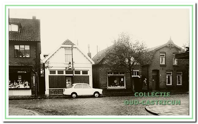 Omstreeks 1960 genomen foto van een gedeelte van de Burg. Mooijstraat met van links naar rechts een gedeelte van de drogisterij van IJsbrand van Exter, de winkel van juwelier Plas (nr 24), de winkel van zilversmid Latjes (nr 26) en het woonhuis van Niek Jacobs (nr 28).