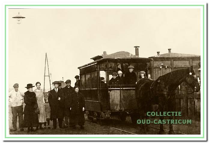 De paardentram met passagiers nabij de spoorwegovergang naar de Mient met op de achtergrond het seinwachtershuisje.