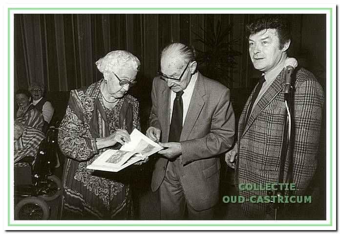 Henk Heideman (rechts) reikt zijn nieuwe boekje uit aan Mevrouw Bot.